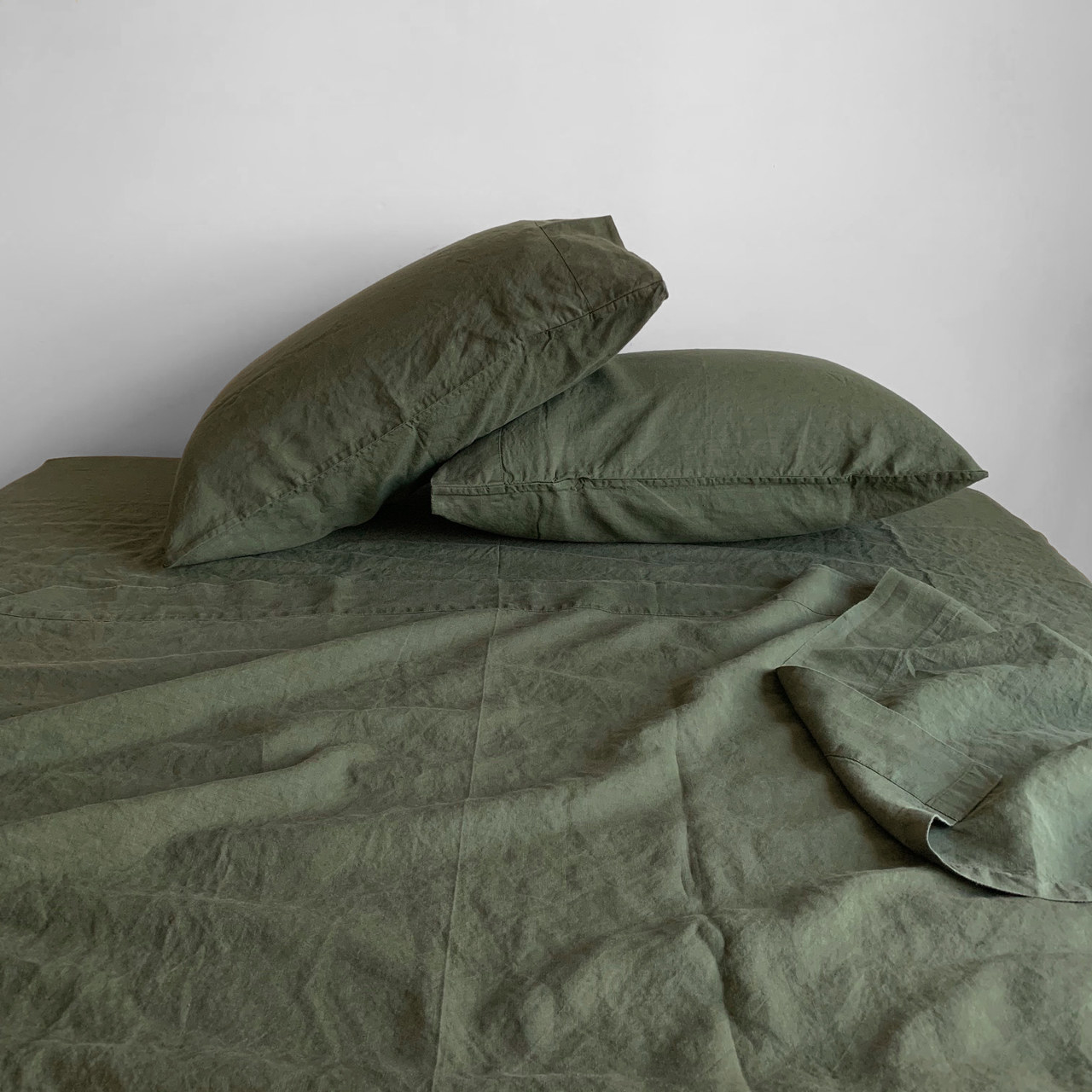 olive sheets on a bed