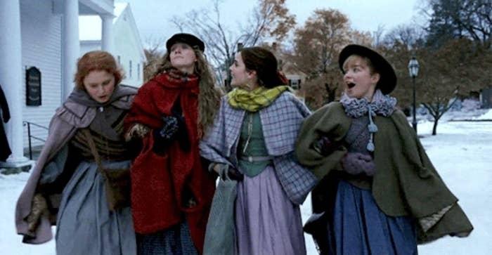 Beth (Eliza Scanlen), Jo (Saoirse Ronan), Meg (Emma Watson), and Amy (Florence Pugh) March take a stroll arm-in-arm through their snowy town in some cozy looking winter wear.