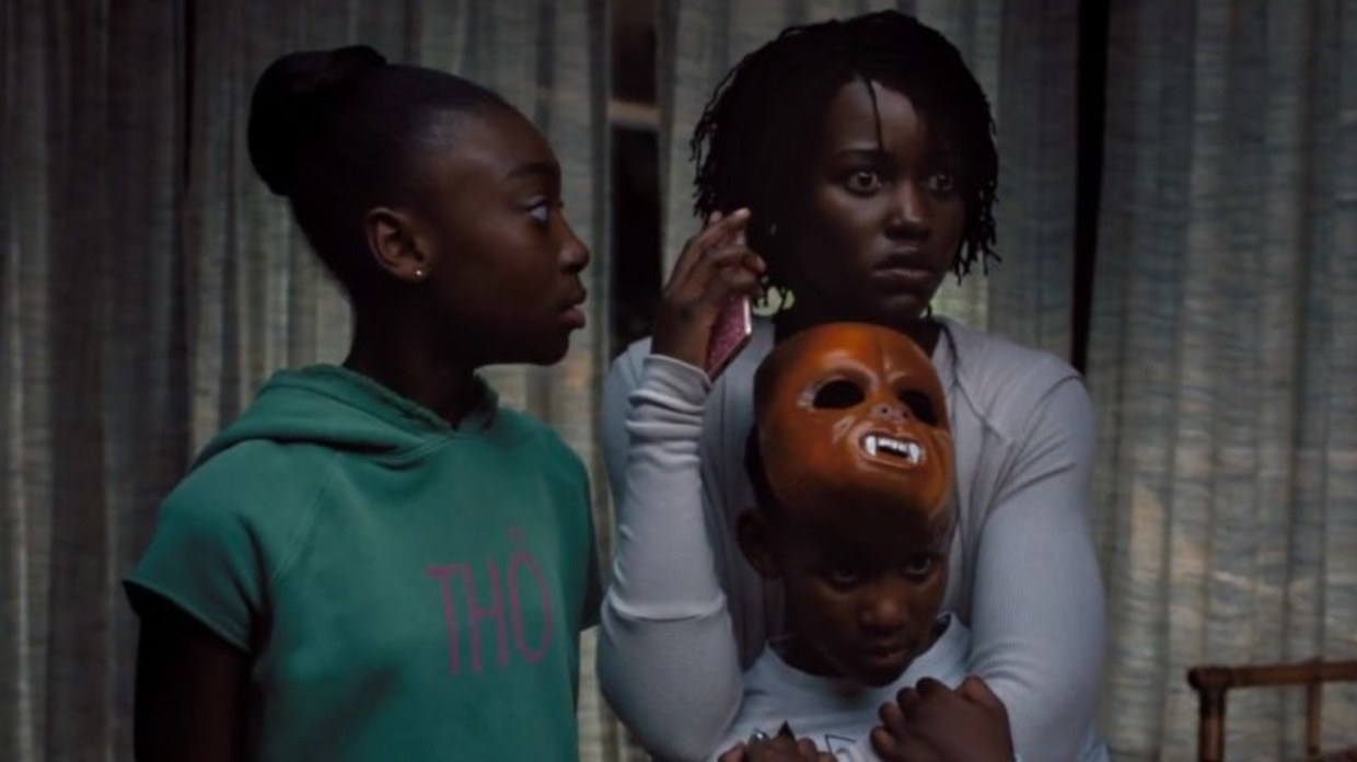 Adelaide Wilson (Lupita Nyong'o) protects her children, Zora (Shahadi Wright Joseph) and Jason (Evan Alex), while trying to contact the police.