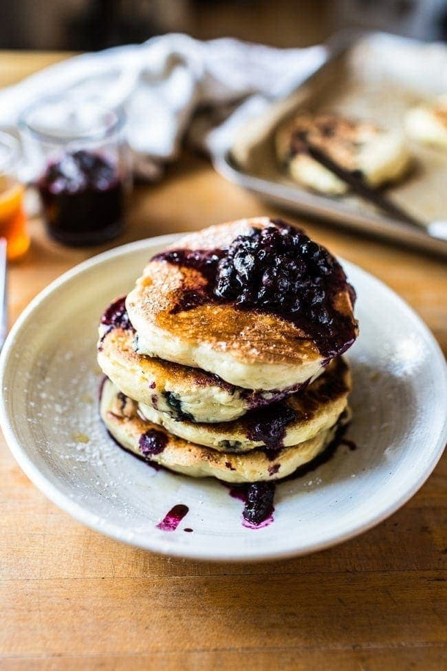 A stack of thick and fluffy blueberry pancakes with blueberry compote on top.