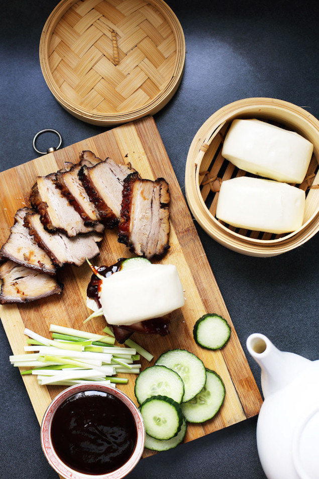 A wooden cutting board topped with barbecue pork, bao buns, scallions, cucumber, and hoisin sauce.