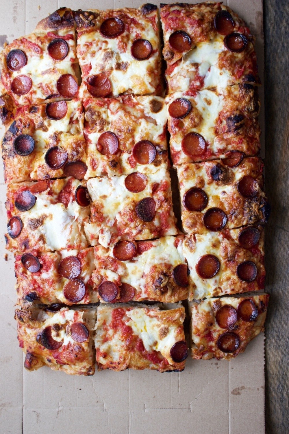 A thick crust Sicilian pizza with charred edges topped with pepperoni.