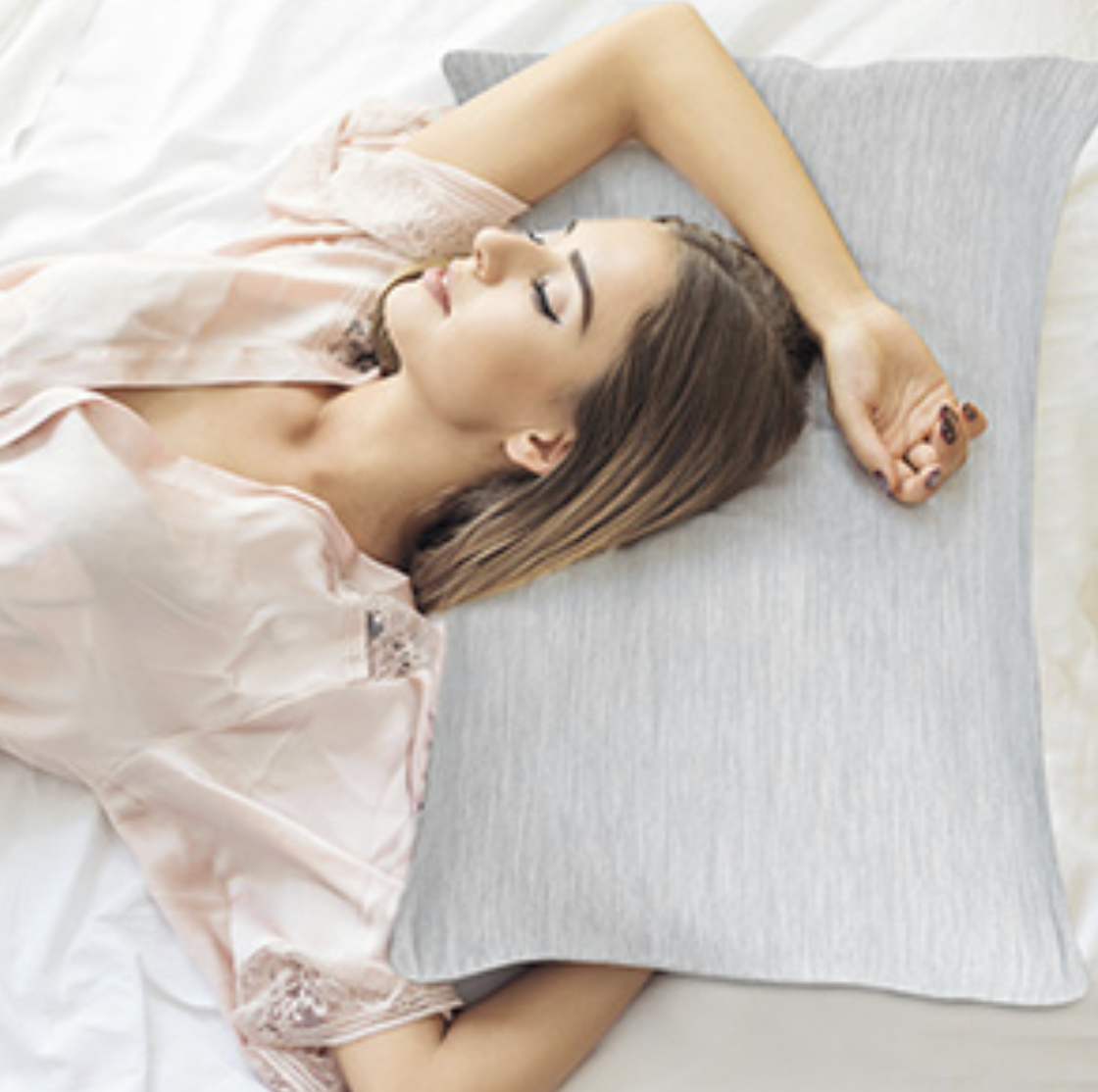 A model laying on a gray pillow