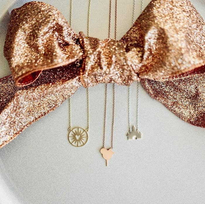 a gold necklace designed to look like the Disney ferris wheel, a rose gold necklace designed to look like a mickey ice cream bar, and a silver necklace of sleeping beauty castle