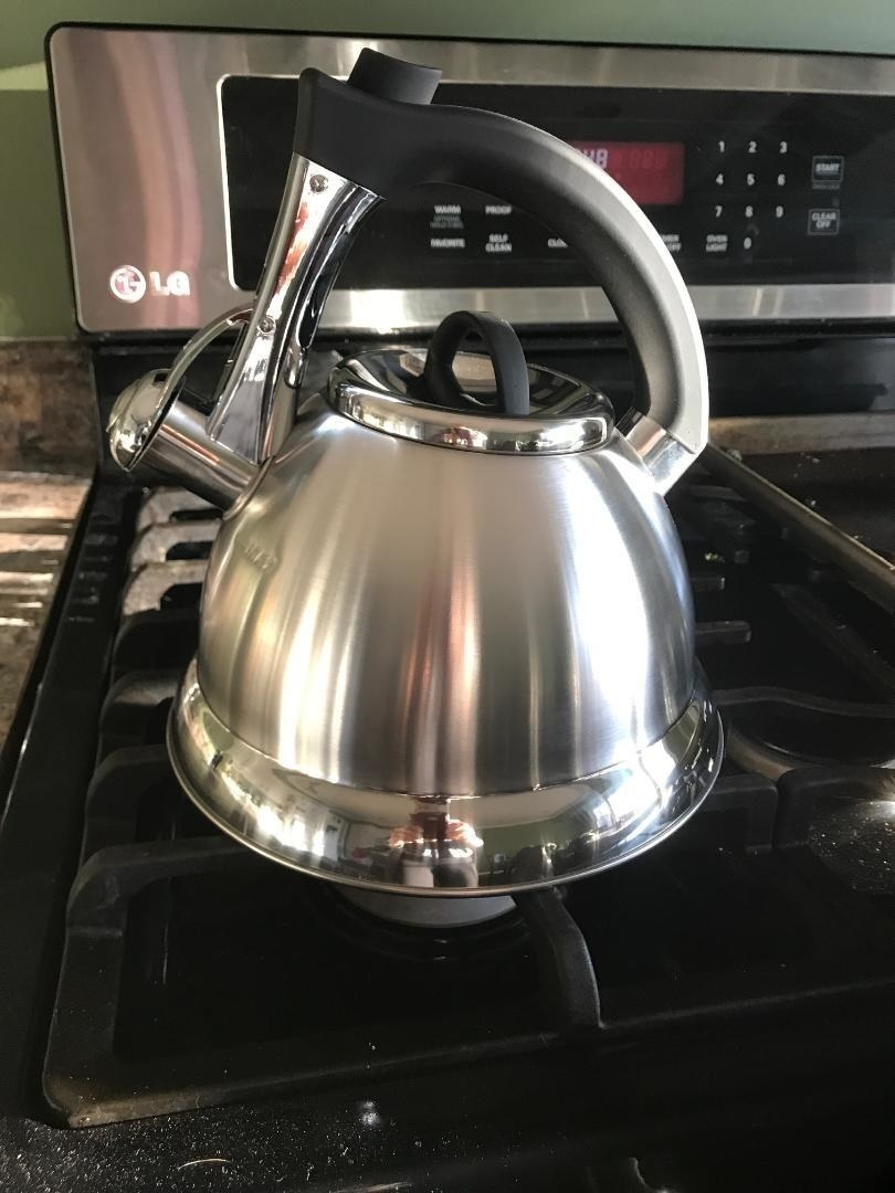 A shiny metallic tea kettle with a black handle sitting on a stovetop