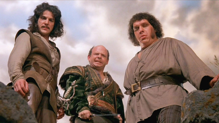 Inigo (Mandy Patinkin), Vizzini (Wallace Shawn), and Fezzik (André the Giant) look down at a mysterious approaching man.