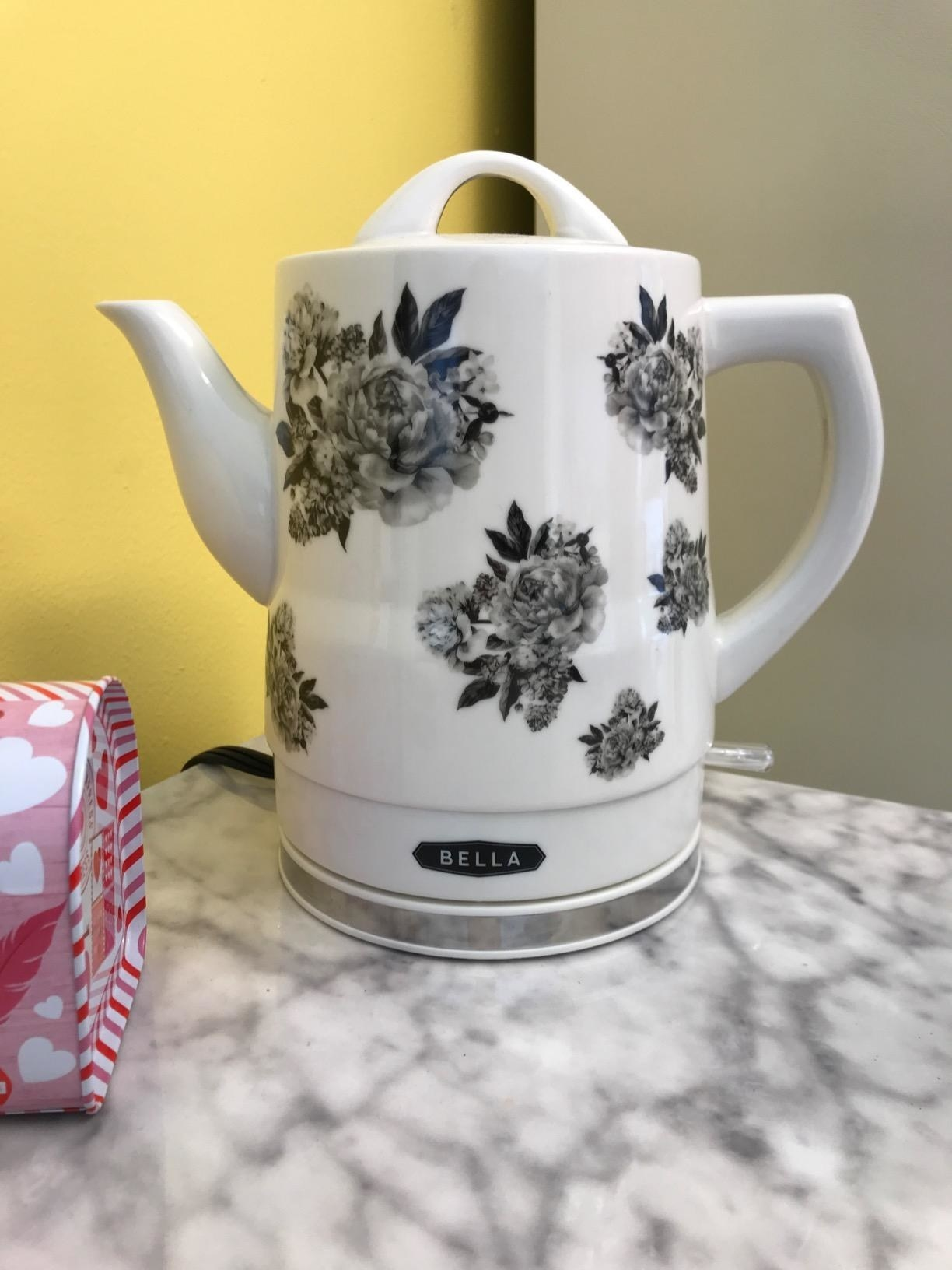 A white electric kettle with black floral designs all over it
