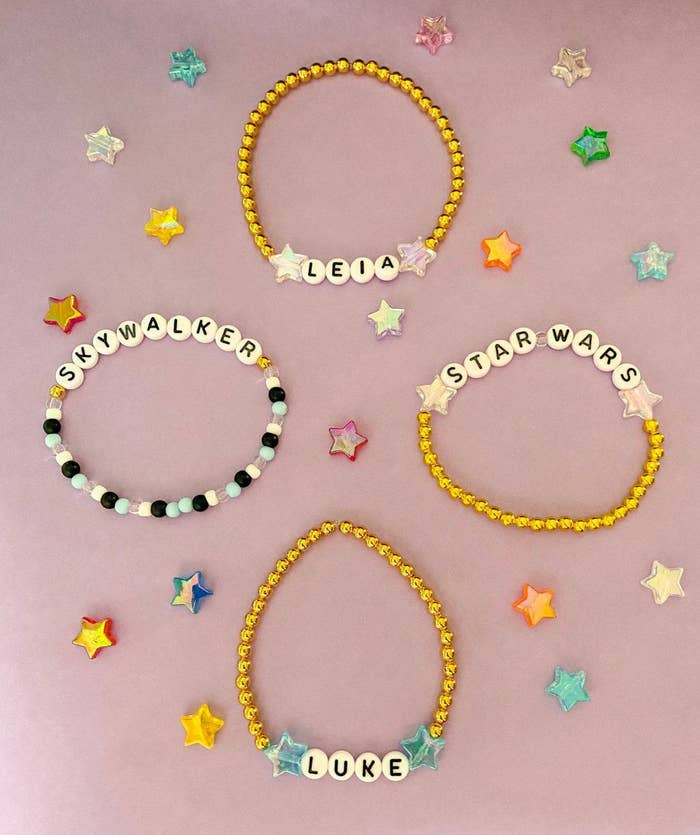 a set of four beaded bracelets spread out, one says leia, one says skywalker, one says star wars, and one says luke