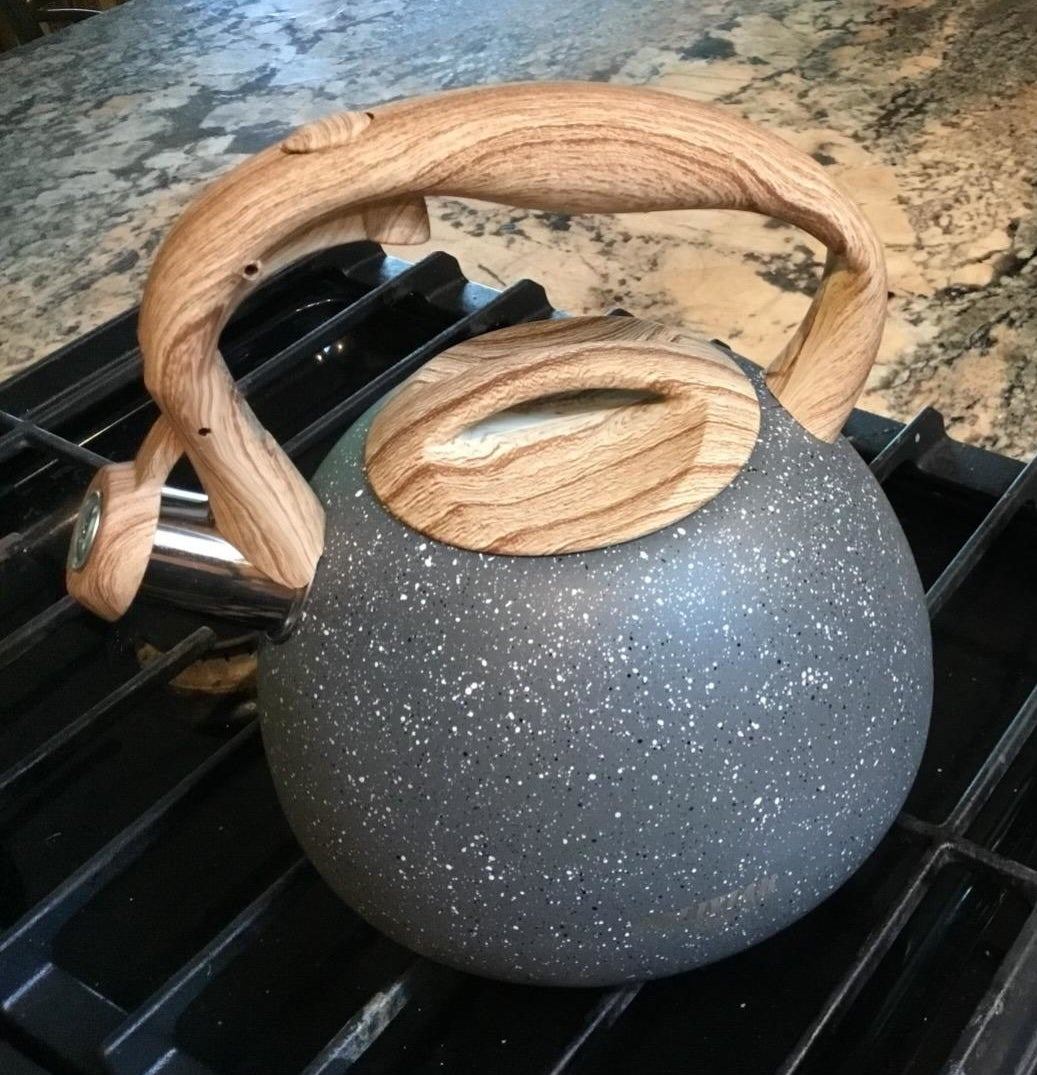 A black tea kettle with white speckles, a metallic spout, and a faux-wood handle