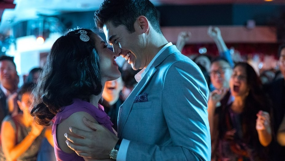 Rachel (Constance Wu) and Nick (Henry Golding) embrace in front of a cheering crowd of family and friends.