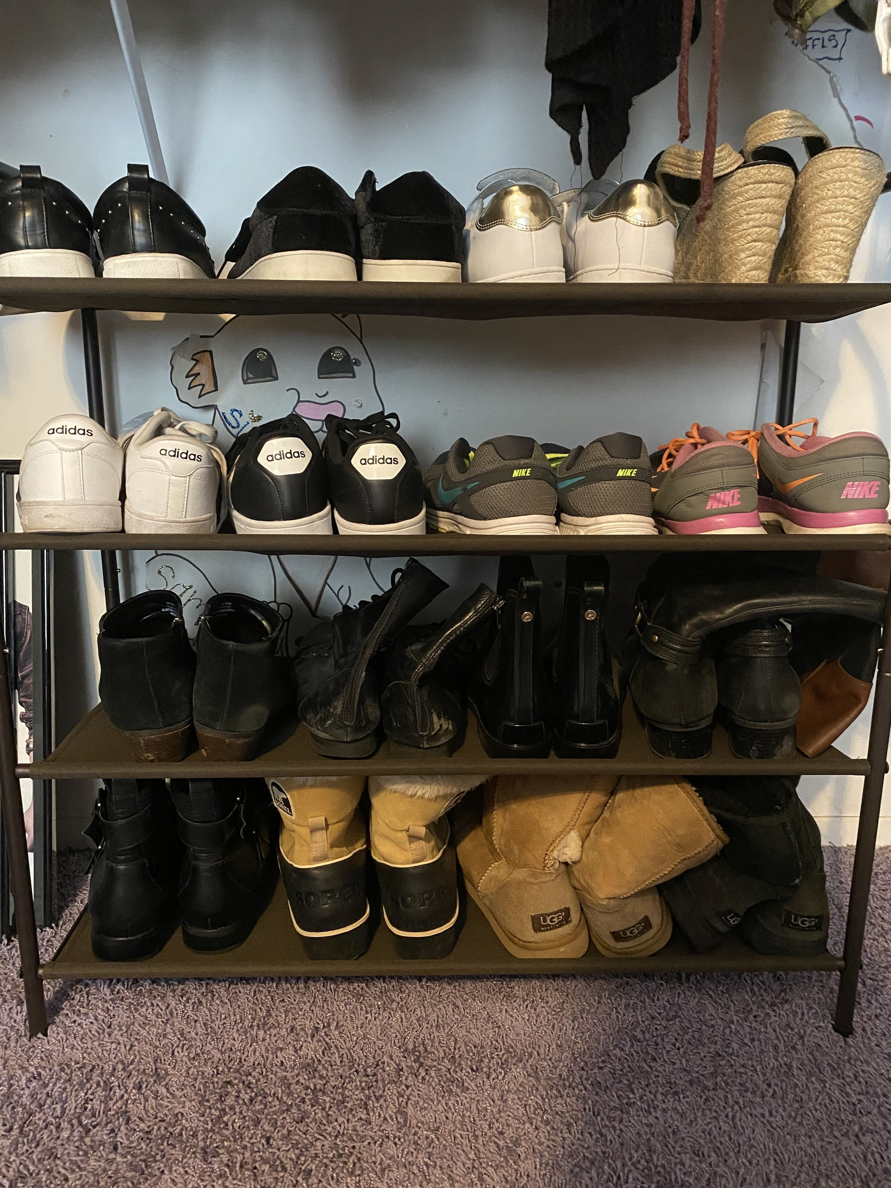 The four-tier shoe rack in bronze in Sam's closet, with four pairs on each shelf