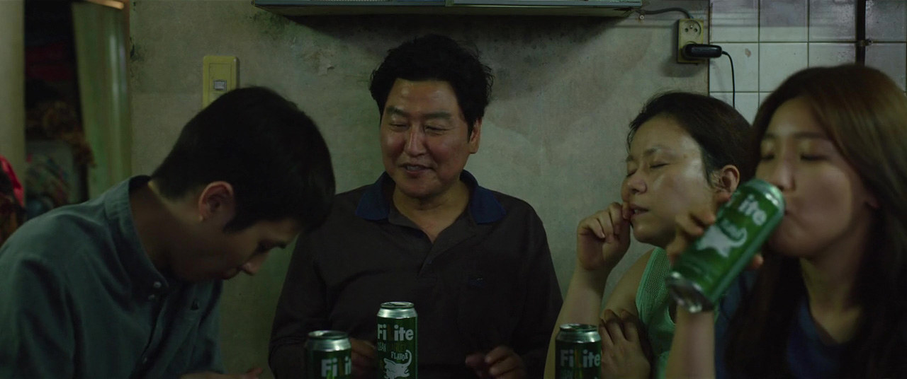 The Kim family (from left to right: Choi Woo-shik, Song Kang-ho, Jang Hye-jin, and Park So-dam) chat and enjoy drinks together in their home.