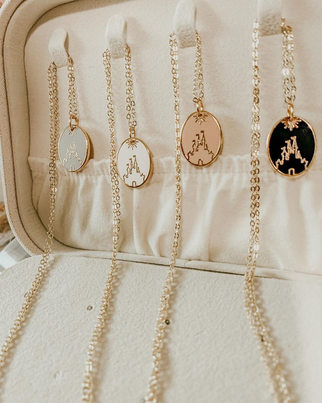 four versions of the same necklace: each in has a charm of cinderella castle in a different color