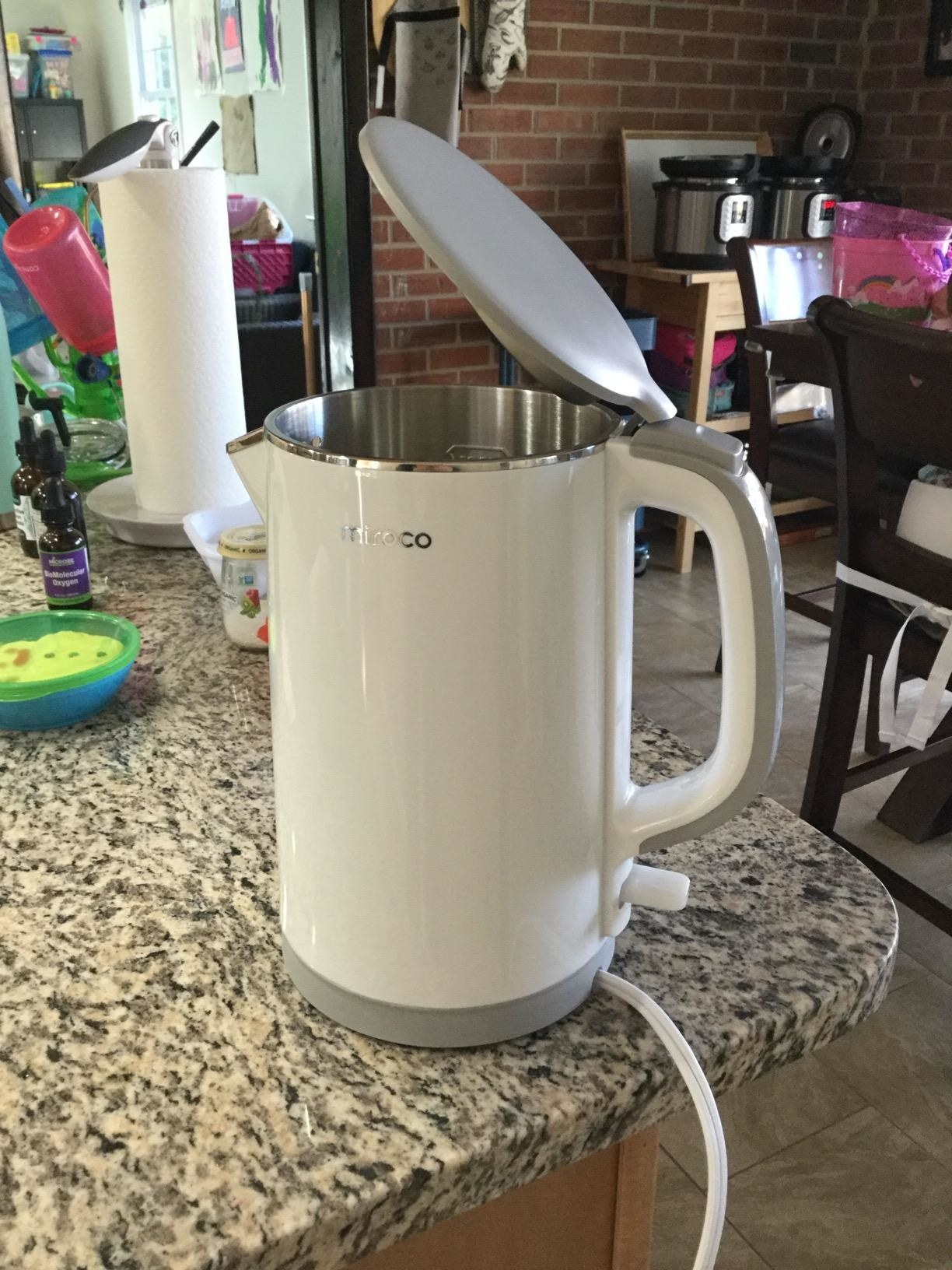 A white electric tea kettle with a gray top and grat accents at the base and handle