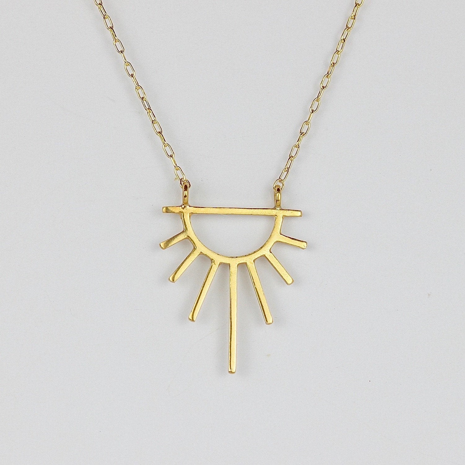 Geometric gold sun necklace against grey backdrop