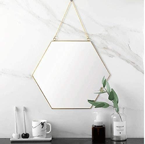 The hexagon wall mirror hanging in a bathroom.