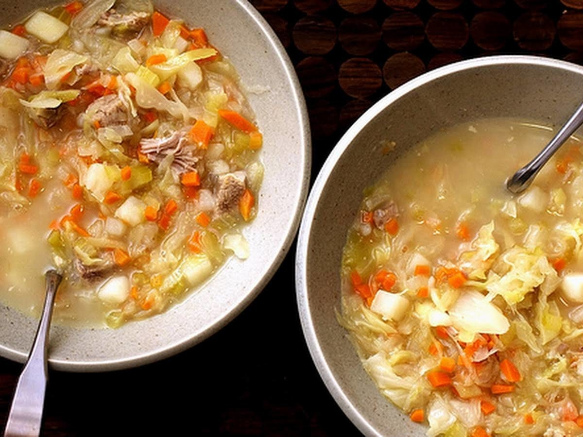 Two bowls of cabbage soup with carrots, pork, celery, and potatoes.