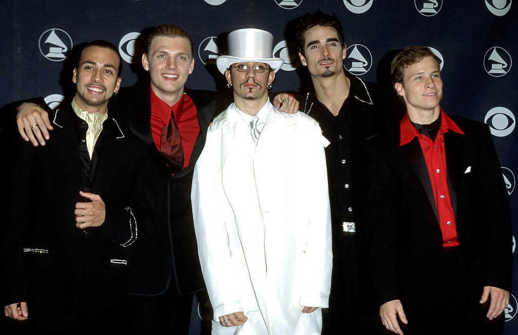 A.J. McLean wearing an oversized white suit being surrounded by the other Backstreet Boys