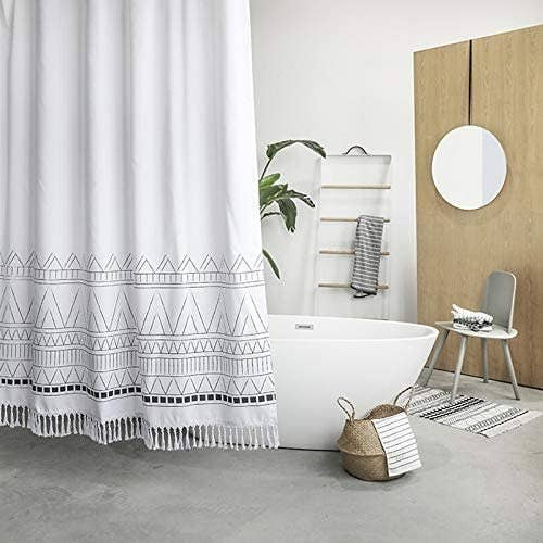 The fabric shower curtain with a triangle design across the bottom third and fringe across the bottom hanging around a bathtub.