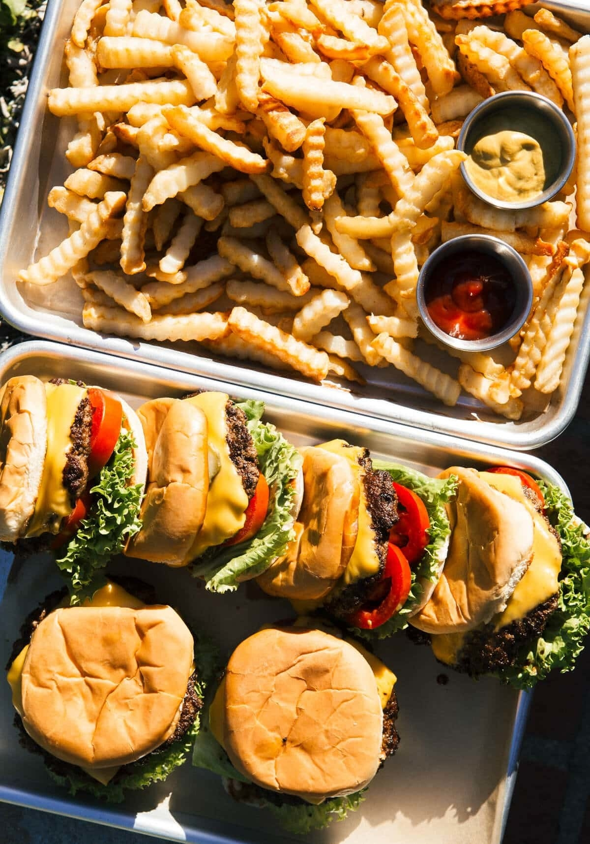 A platter of shake shack inspired cheeseburgers with lettuce and tomato and crinkle-cut fries.