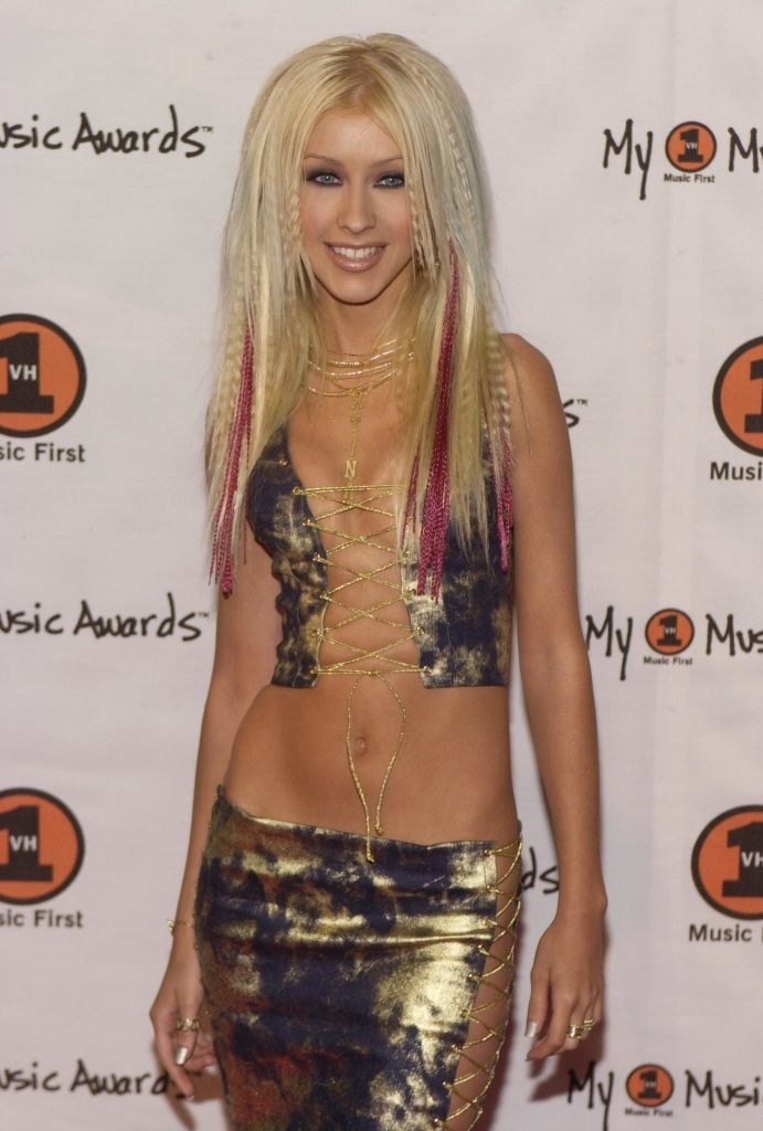Christina Aguilera with a metallic outfit and crimped hair.