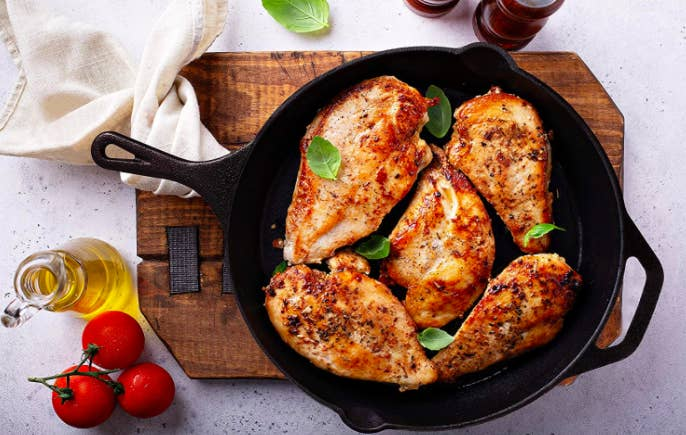 A black cast iron skillet filled with grilled chicken breasts and basil leaves