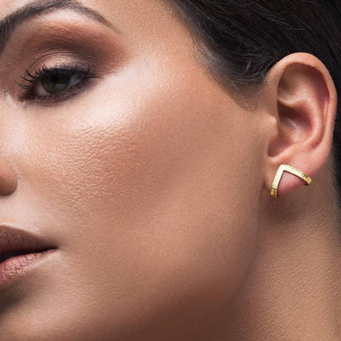 A model wearing one of the stud earrings in the gold finish. It wraps slightly around the back your earlobe and forms a point about where your piercing is, so it's a stud that looks like a cuff