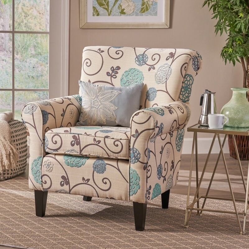 The armchair, which is cream colored and features a pattern of brown and pale blue  vines and medallions.