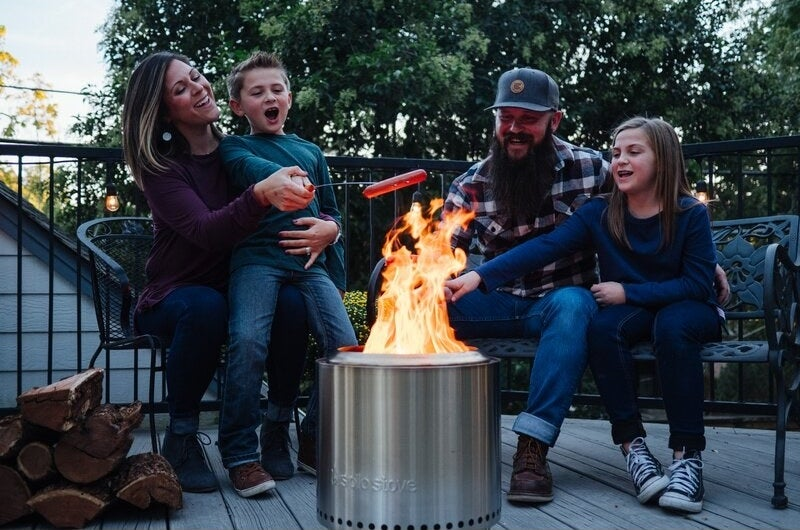 Family using the fire pit to cook hot dogs on a stick