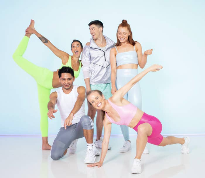 A group of five workout instructors posing and smiling