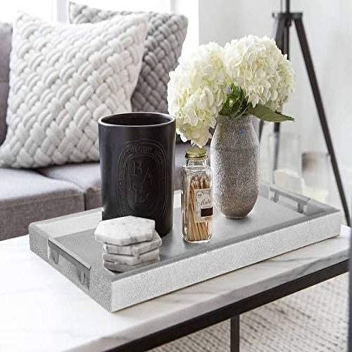 The decorative tray on a table with decor neatly arranged on top of it.