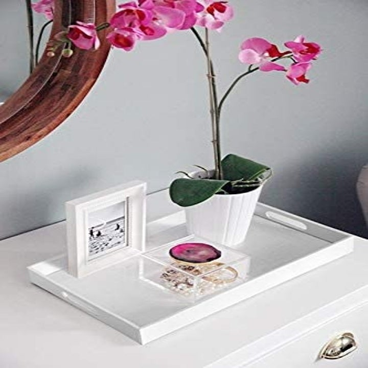 The decorative tray on a side table with decor neatly arranged on top of it.