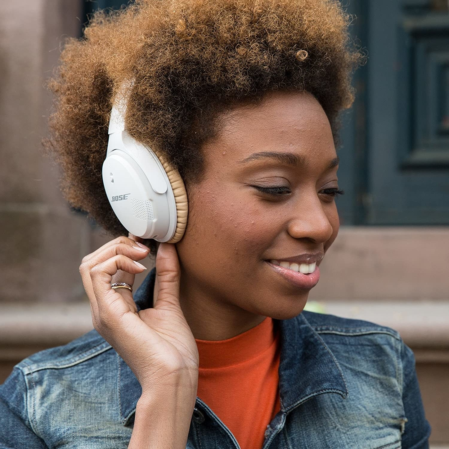 A person adjusting the volume on the Bose Bluetooth headphones