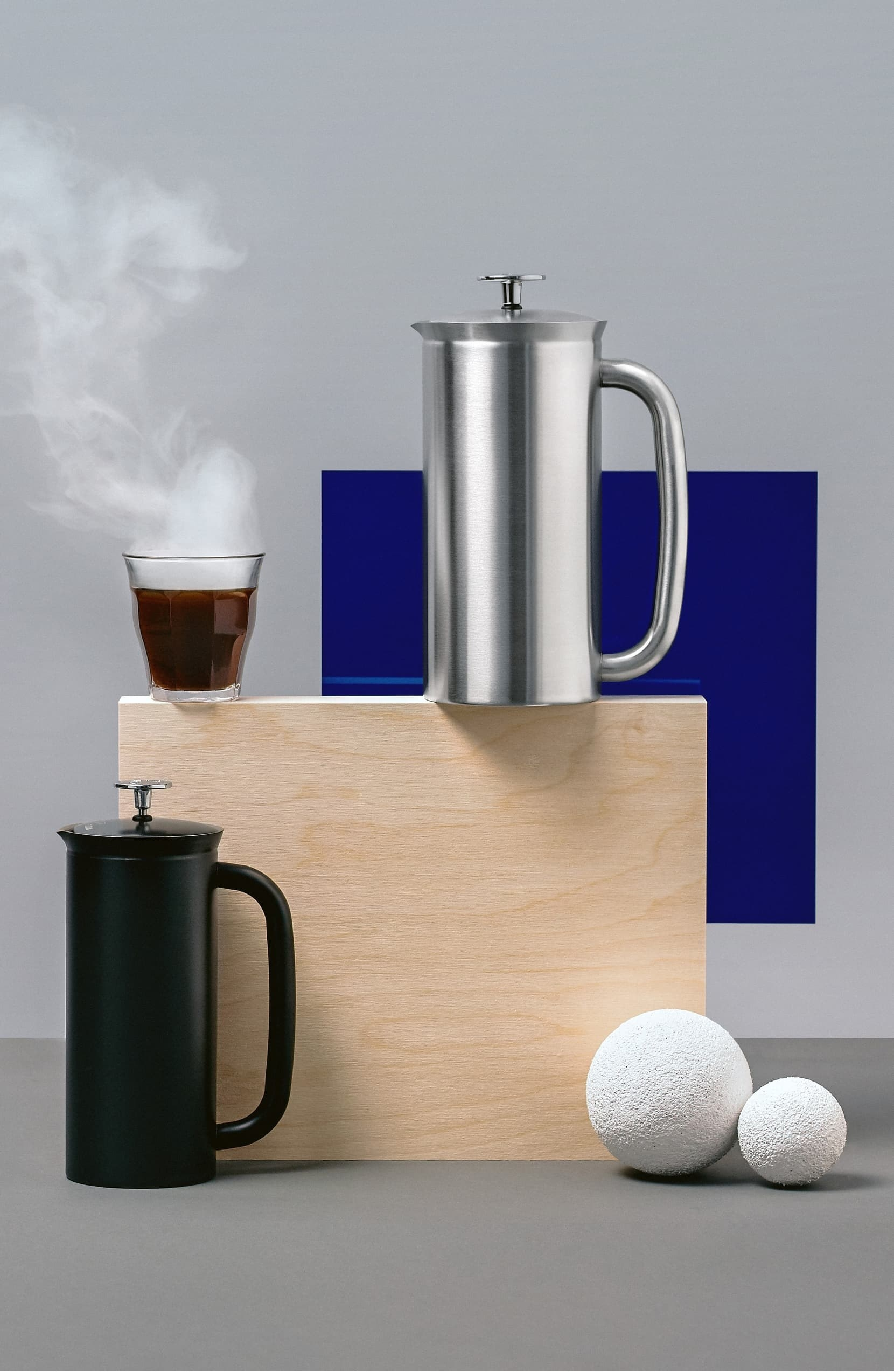 Black French press and stainless steel French press displayed on wood block with coffee