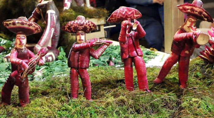 Three human figures (carved out of radishes) wearing sombreros and playing musical instruments