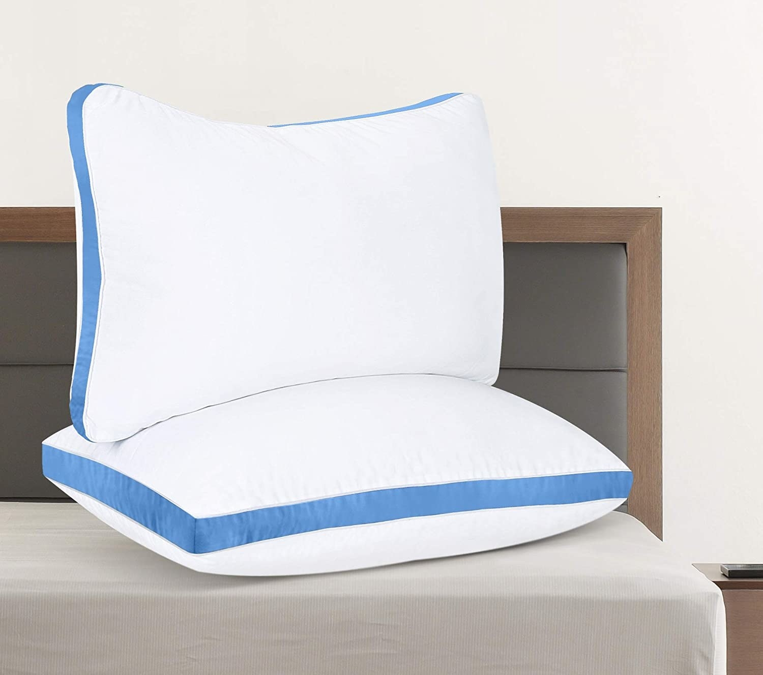 Two quilted pillows stack on top of each other on a bed