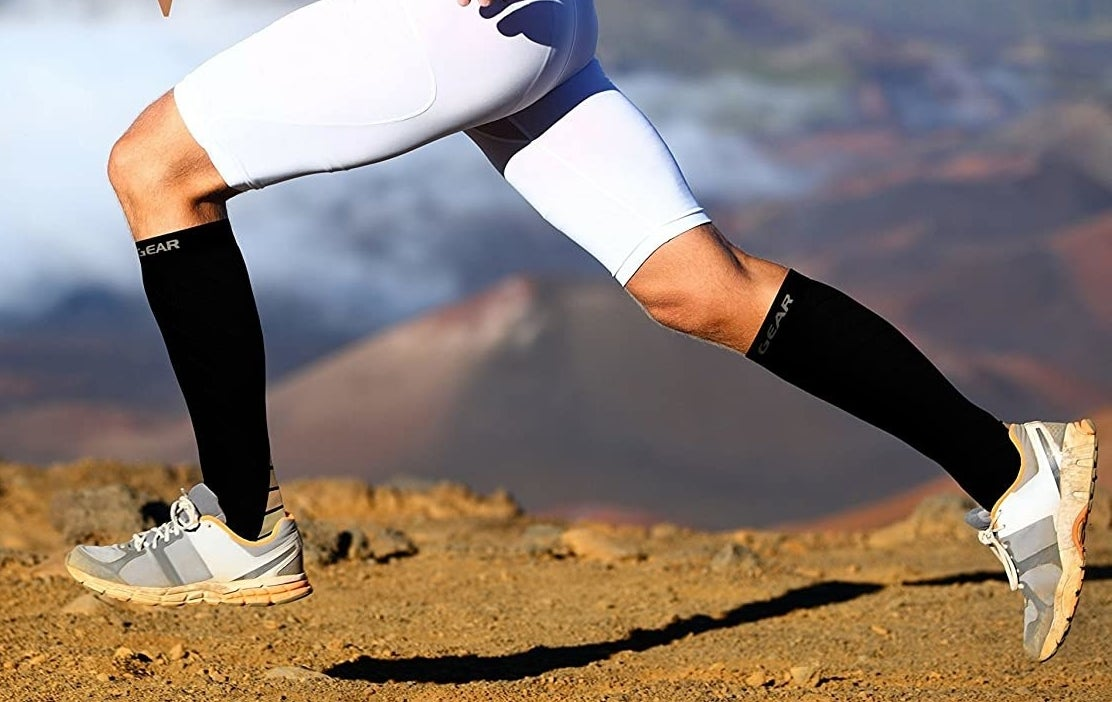 A person running on a dirt road while wearing the compression socks and shorts