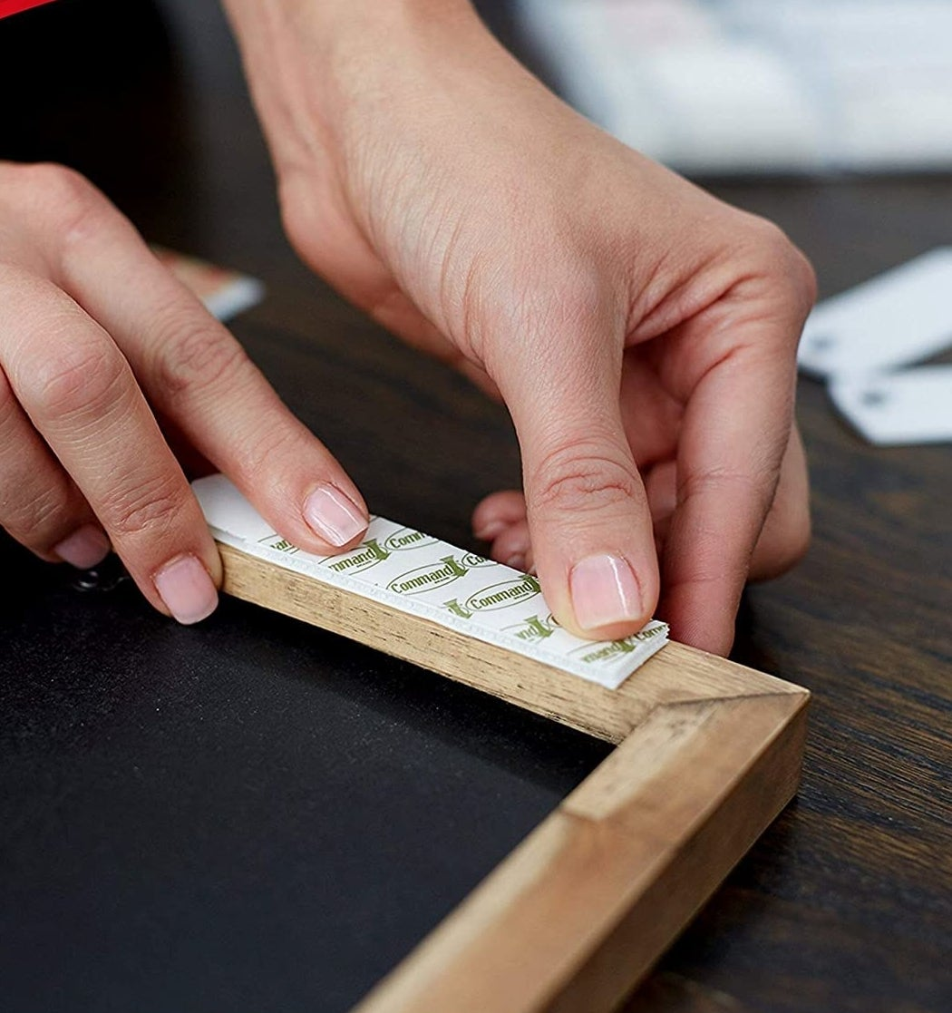 A person putting a Command strip on the back of a frame