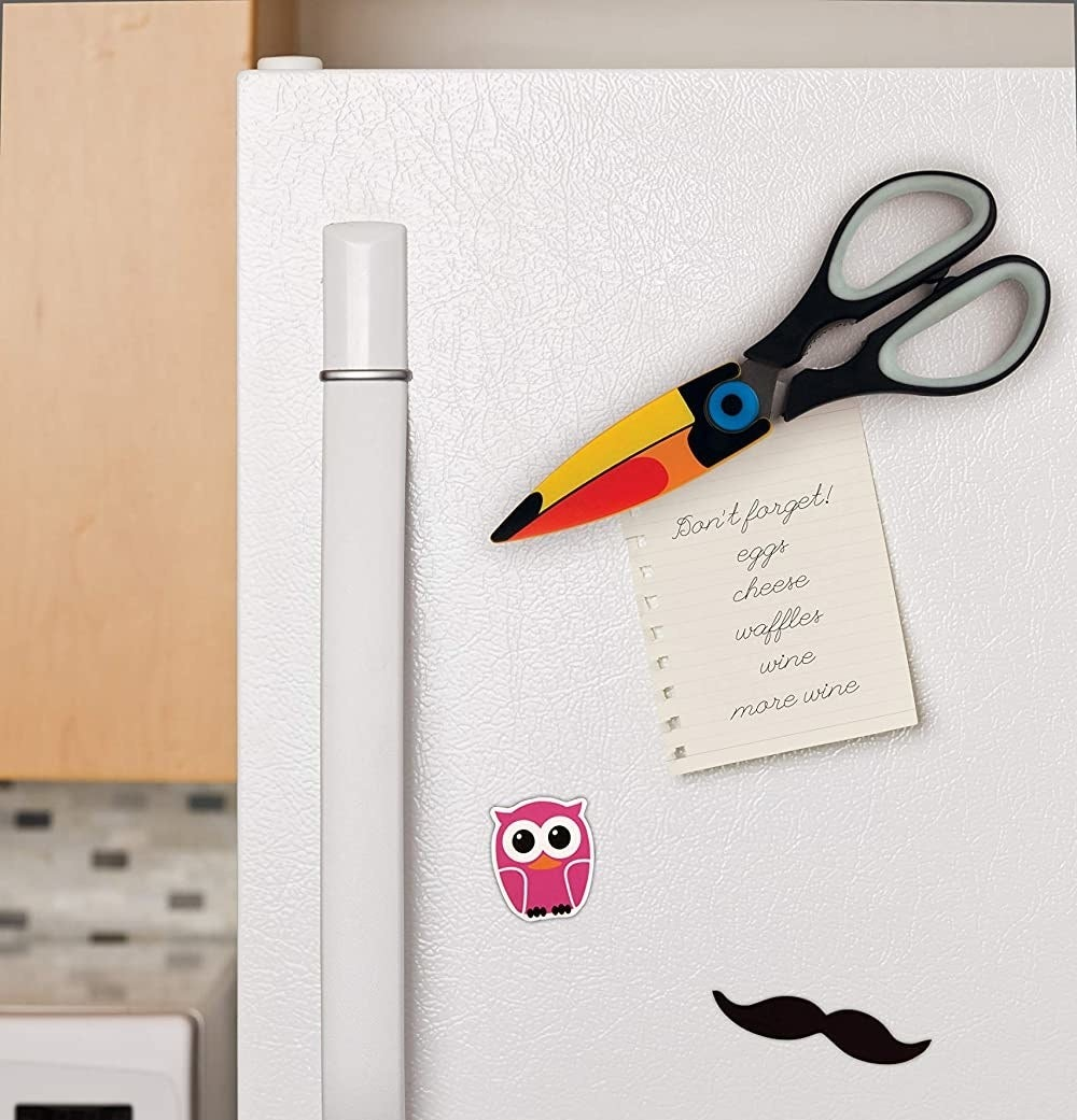 Toucan-shaped scissors are seen attached to a fridge door, holding up a grocery list