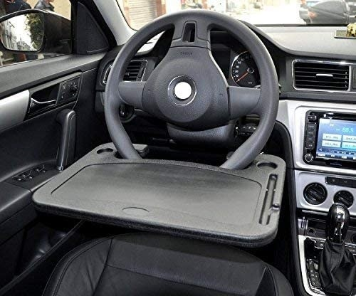 The tray table attached to a steering wheel inside of a car