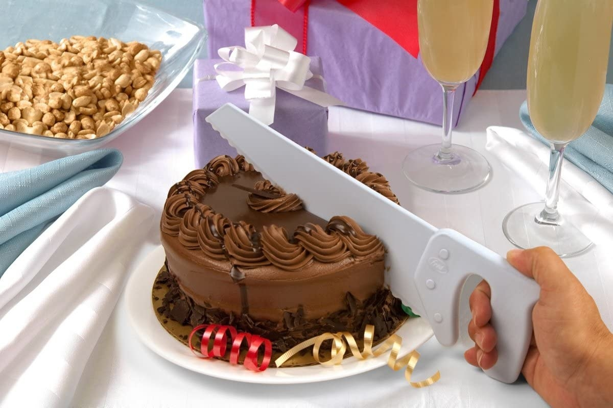 A hand saws a dark chocolate cake in half using the cake saw