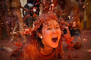 Woman in a crowd absolutely covered in tomatoes (and their juices) at a tomato festival in Spain