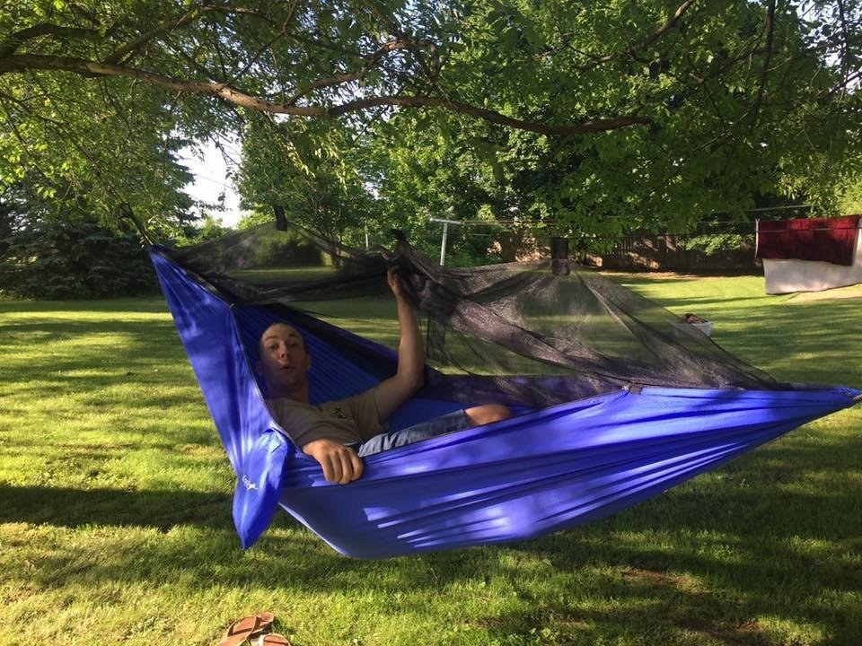 reviewer in hammock shows the mesh covering