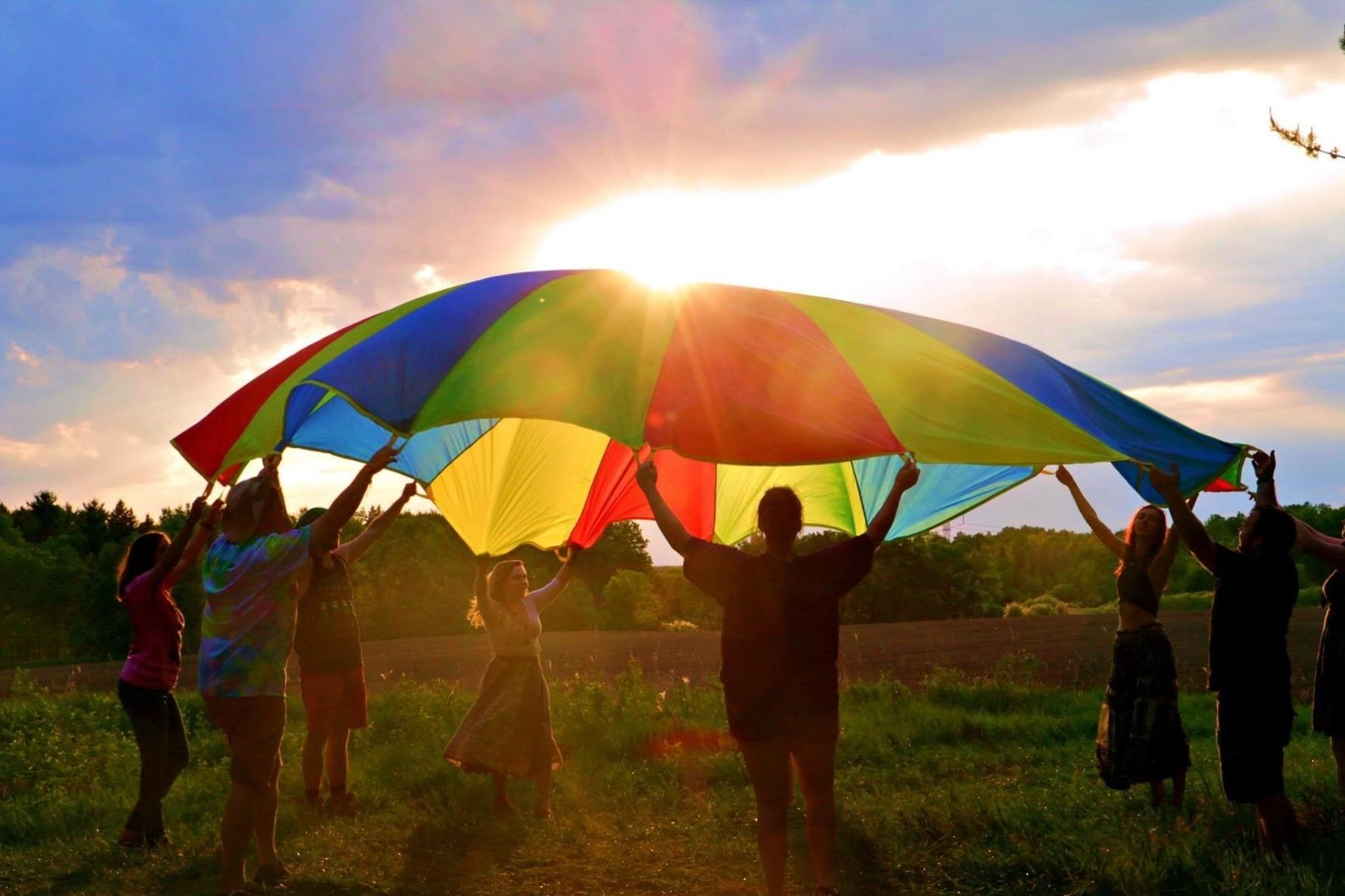 review photo of adults throwing parachute in the air by handles, making it puff up