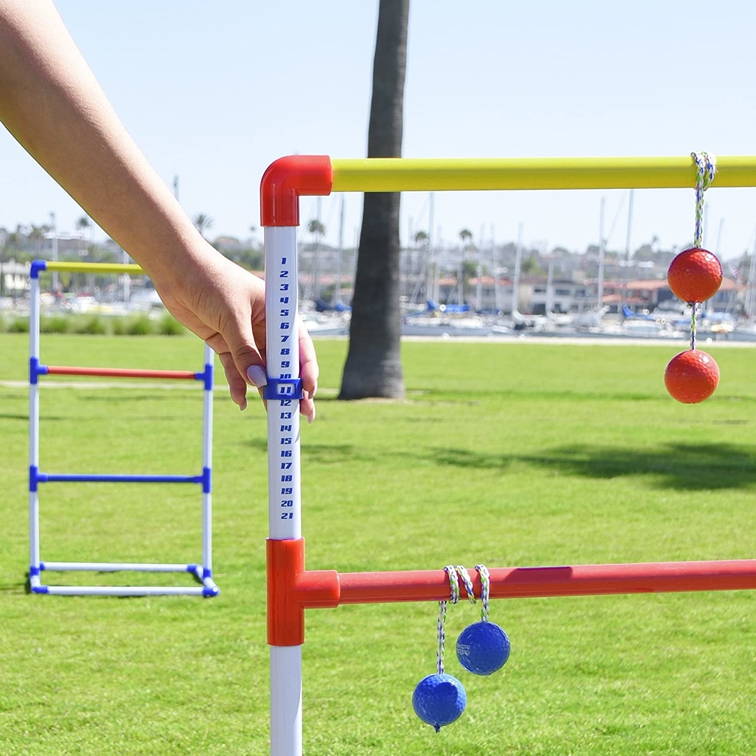 model slides the market on the score keeper on the ladder while two pairs of balls connected with string dangle on the rungs