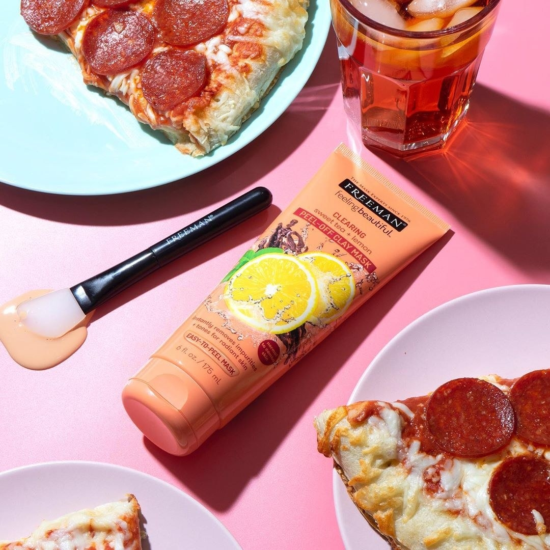 A bottle of the peel-off mask lies on a table next to slices of pizza and a glass of iced tea