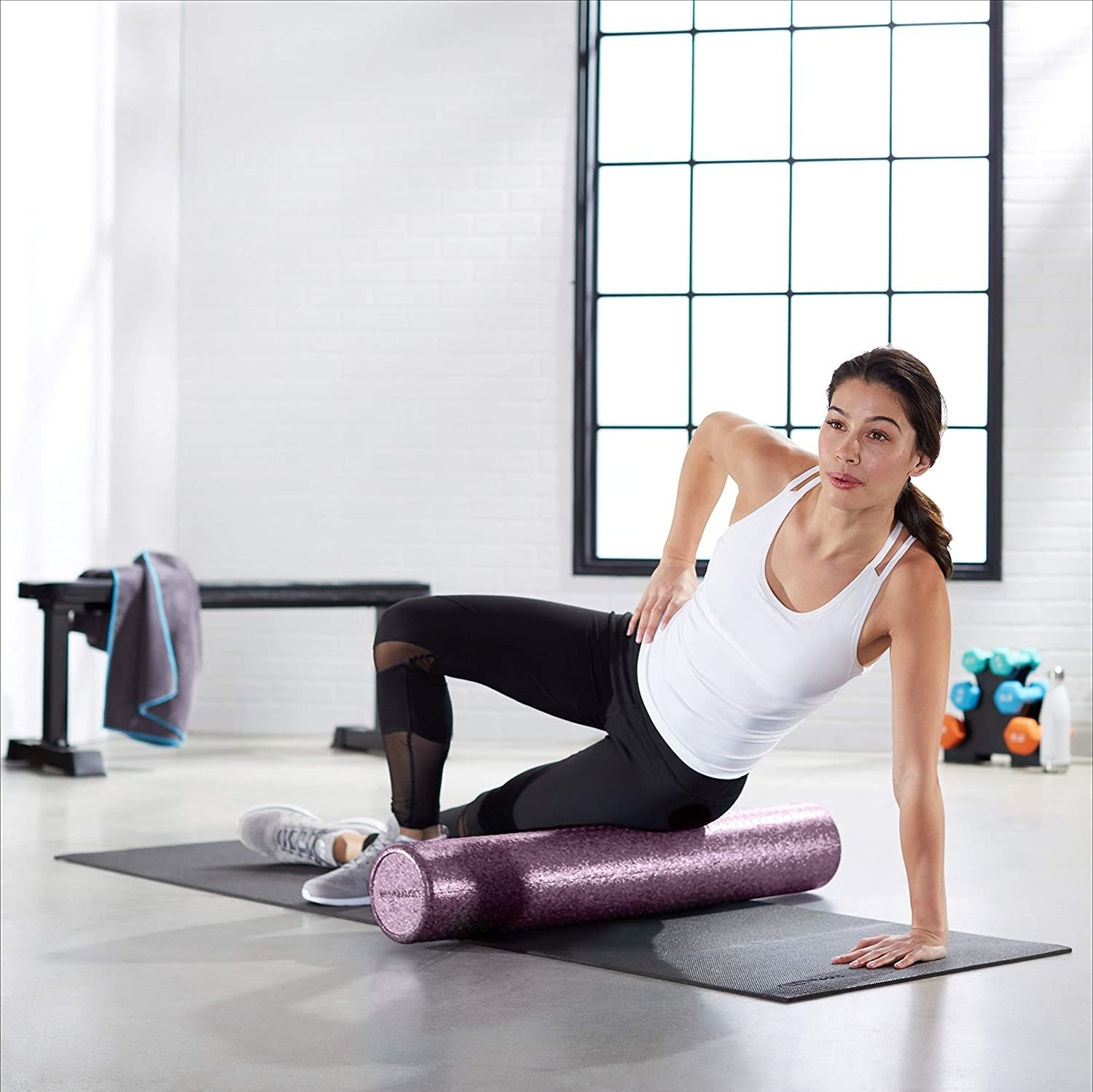 A model working out using the 36-inch purple roller to roll out their leg