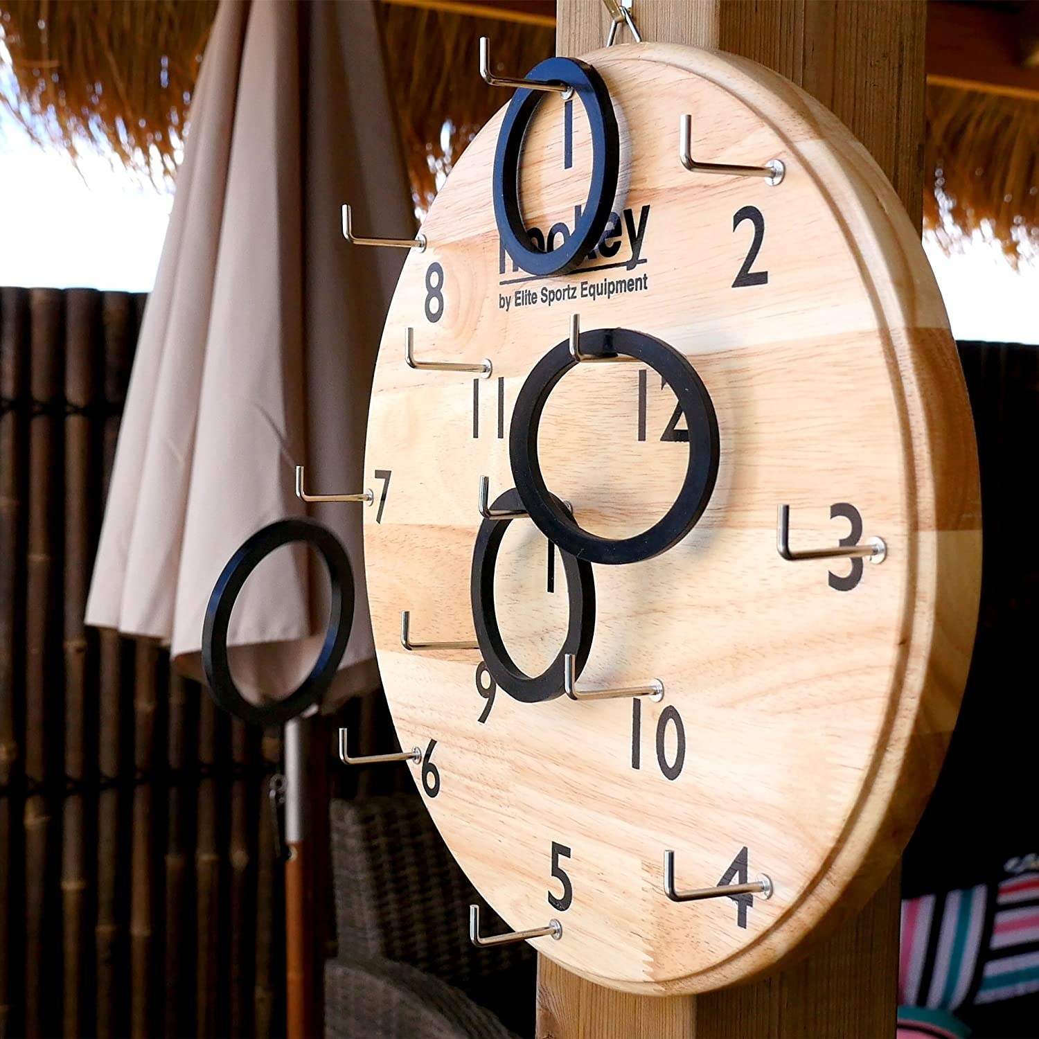 circular wooden board with hooks and numbers. black rings hang from some of the hooks