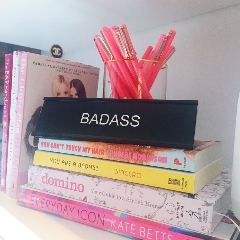 "A black desk plate that reads ""BADASS"" in white letters, atop a stack of books"