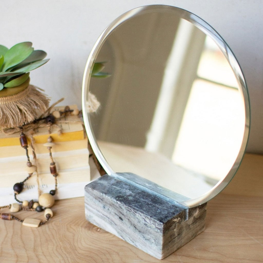 An oval-shaped mirror, just over a foot tall, propped in a marble block stand